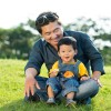 Asian man and his little son sitting on the grass