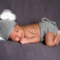 Thirteen day old smiling newborn baby boy wearing a gray crocheted elephant hat and diaper cover. He is sleeping on his stomach on gray fleece fabric.