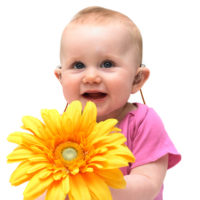 Cute baby girl sits against white background holding large yellow flower