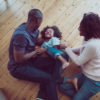 A photo of happy parents tickling son on hardwood floor. High angle view of family are enjoying in new house. They are in casuals. Young parents playing with child at home.