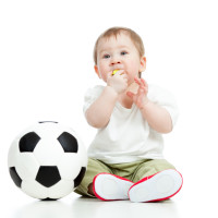 adorable baby football player with ball and whistle over white b