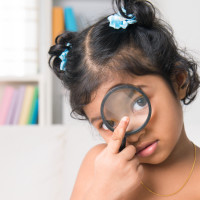 Indian girl peers at the camera through a magnifying glass