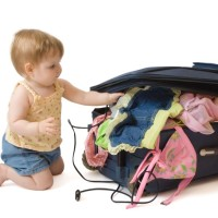 Baby girl kneeling near the suitcase, trying to pack it, isolated