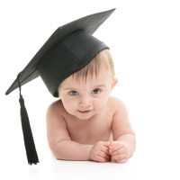 A Portrait of a sitting baby with a graduation cap