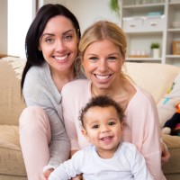 Female couple sit together with their son in their home and all smile for the camera