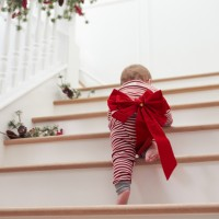Toddler With Christmas Bow On Stairs In Pajamas