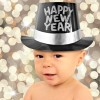 One year old baby boy wearing a Happy New Year top hat.
