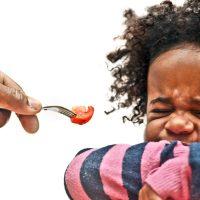 girl grimacing at her food